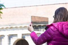 Femme dans une ville prenant des photographies avec le comprimé transparent Image libre de droits