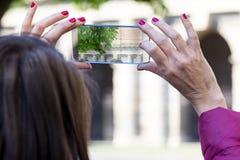 Femme dans une ville prenant des photographies avec le téléphone transparent Image libre de droits