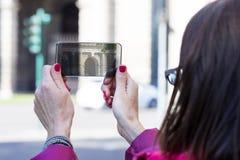 Femme dans une ville prenant des photographies avec le téléphone transparent Photos stock