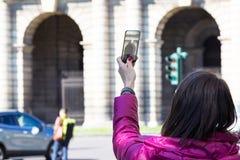 Femme dans une ville prenant des photographies avec le téléphone transparent Photo libre de droits