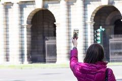 Femme dans une ville prenant des photographies avec le téléphone transparent Photographie stock