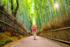 Femme dans Yukata traditionnel avec le parapluie rouge à la forêt en bambou o Photos stock