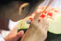 Femme découpant une pastèque Images stock