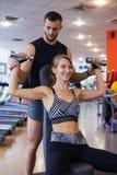 Femme de aide d'entraîneur personnel fléchissant des muscles dans le gymnase photos libres de droits