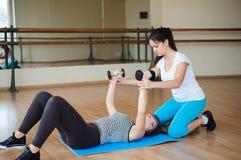 Femme de aide d'entraîneur personnel pour faire des exercices avec des haltères dans le gymnase image stock
