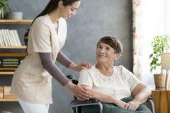Femme de aide d'infirmière dans le fauteuil roulant Image stock