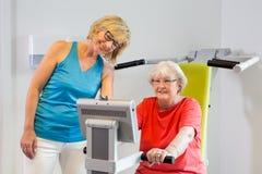 Femme de aide d'instructeur avec la machine d'exercice Photos libres de droits