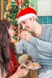 Femme de alimentation d'homme avec les biscuits ou le gâteau doux d'un plat Image libre de droits