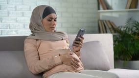 Femme de attente triste mettant en rouleau l'appli de smartphone, fatigue de grossesse, malaise banque de vidéos