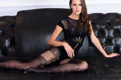 Femme de attirance sexy dans la combinaison noire séduisante de lingerie sur le divan en cuir Photo stock
