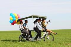 Femme de Baloons menant 4 types sur un vélo de quadruple un jour ensoleillé de champ vert Photographie stock libre de droits
