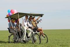 Femme de Baloons menant 4 types sur un vélo de quadruple un jour ensoleillé de champ vert Photos stock