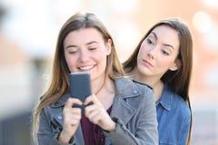 Femme de bavardage remarquant le téléphone d'un ami photo stock