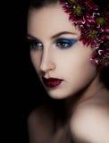 Femme de beauté avec des fleurs sur le fond noir Image libre de droits