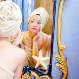 Femme de beauté avec l'essuie-main regardant le miroir d'or Photo libre de droits