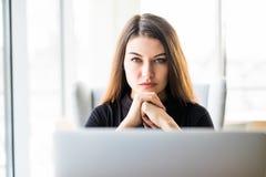 Femme de beauté avec l'ordinateur portable dans le regard avant à l'appareil-photo dans le bureau Photos libres de droits