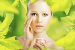 Femme de beauté avec les soins de la peau crèmes et naturels en vert Photos libres de droits