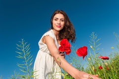Femme de beauté dans le domaine de pavot dans la robe blanche tenant un bouquet de pavots image stock
