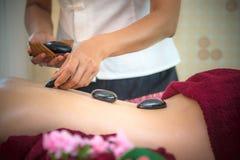 Femme de beauté de l'Asie se couchant sur le lit de massage avec l'alon chaud de pierres de balinese traditionnel Photo stock
