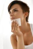 Femme de beauté nettoyant la belle peau fraîche avec le tissu absorbant Images stock