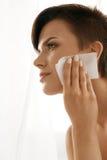 Femme de beauté nettoyant la belle peau fraîche avec le tissu absorbant Photo libre de droits