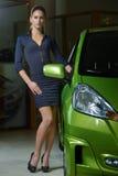 Femme de beauté posant près de la voiture de fantaisie de couleur verte Photo stock