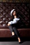 Femme de beauté posant sur le sofa en cuir dans l'obscurité Photo stock