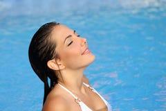 Femme de beauté respirant tout en se baignant dans une piscine en été Images stock