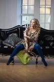 Femme de beauté dans le sofa luxueux avec le sac à main Images libres de droits