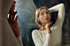 Femme de Beautful dans la robe blanche au miroir. Image stock