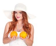 Femme de Beautuful avec de longs cheveux rouges posant dans la robe et le chapeau blancs photographie stock libre de droits