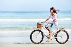Femme de bicyclette de plage photo stock