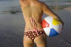 Femme de bikini couverte en sable sur la bille de plage de plage Photos libres de droits