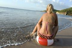 Femme de bikini reposant la plage colorée de beachball Image stock