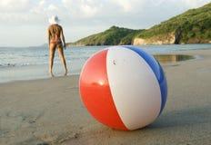 Femme de bikini restant la plage colorée de beachball Photographie stock libre de droits