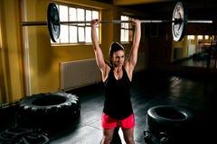 Femme de Bodybuilder faisant l'exercice au gymnase images stock