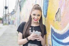 Femme de bonheur avec le téléphone dans la rue avec le graffiti Photo stock