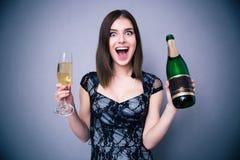 Femme de bonheur jugeant deux en verre et bouteille de champagne Photographie stock