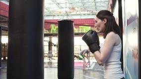 Femme de boxeur faisant quelques séances d'entraînement sur un sac de sable dans le gymnase Fin vers le haut clips vidéos