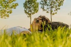 Femme de brune appréciant le mensonge sur elle de retour sur l'herbe verte en nature photos stock