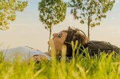 Femme de brune appréciant le mensonge sur elle de retour sur l'herbe verte en nature image stock