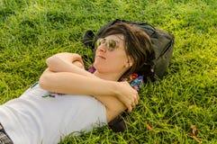 Femme de brune appréciant le mensonge sur elle de retour sur l'herbe verte en nature photographie stock