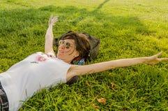 Femme de brune appréciant le mensonge sur elle de retour sur l'herbe verte en nature images libres de droits