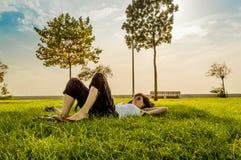 Femme de brune appréciant le mensonge sur elle de retour sur l'herbe verte en nature images stock