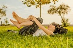 Femme de brune appréciant le mensonge sur elle de retour sur l'herbe verte en nature photo stock
