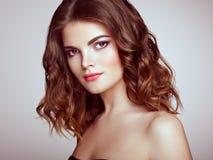 Femme de brune avec de longs cheveux onduleux brillants Photo stock