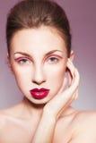 Femme de brune avec de pleines lèvres rouges et lignes rouges sur sa coiffure de paupières et de tresse Image libre de droits