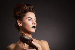 Femme de brune avec l'escargot avec des yeux au beurre noir et des lèvres. Mode. Obtenu Image libre de droits