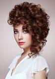 Femme de brune avec les cheveux bouclés et brillants Photographie stock libre de droits