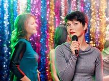 Femme de brune chantant dans le microphone Photographie stock